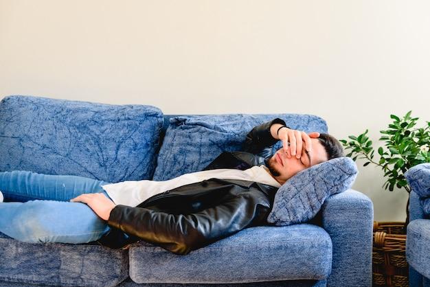 Perturbado jovem deitado no sofá descansando em casa sentindo fadiga, cansado, sofrem de enxaqueca