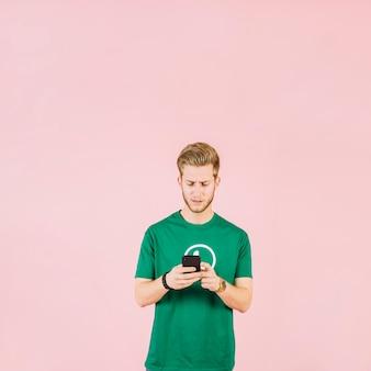 Perturbado jovem usando telefone celular sobre fundo rosa