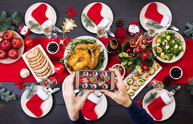 Peru assado. a mesa de natal é servida com um peru, decorado com enfeites brilhantes