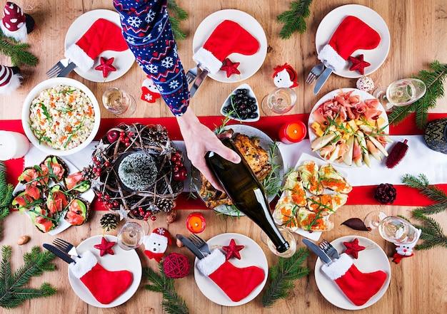 Peru assado. ceia de natal. a mesa de natal é servida com peru, decorada com enfeites brilhantes e velas. frango frito, mesa. jantar em família. vista superior, mãos na moldura