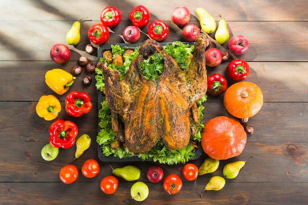 Peru assado com legumes na mesa de madeira