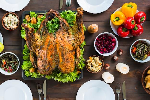 Peru assado com pratos na mesa