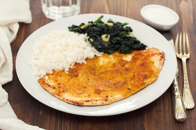Peru frito com arroz e espinafre no prato