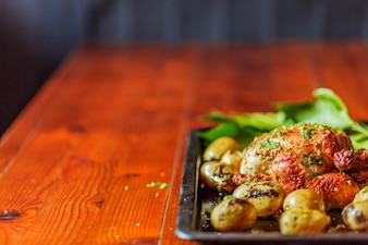 Peru grelhado com batatas e ervas na bandeja na mesa de madeira marrom