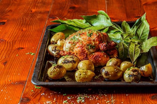 Peru grelhado com batatas e ervas na mesa de madeira