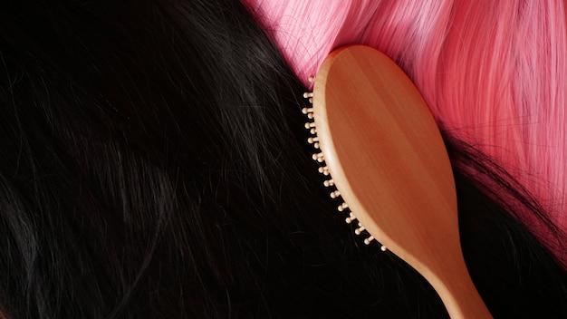 Peruca rosa e preta com cabelo comprido e penteia com pente de madeira. cabeleireiro e cuidados com os cabelos