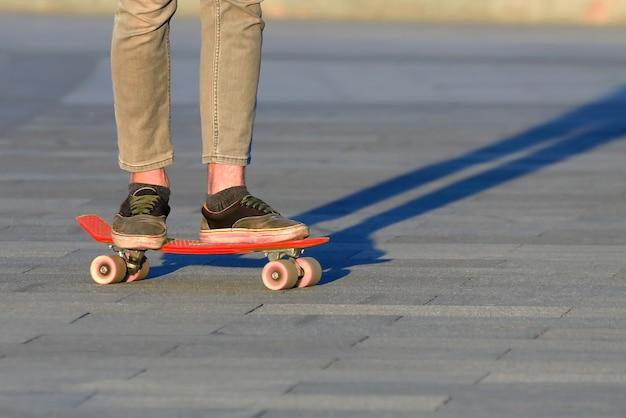 Pés adolescentes de skate na cidade. hobbies e recreação de adolescentes
