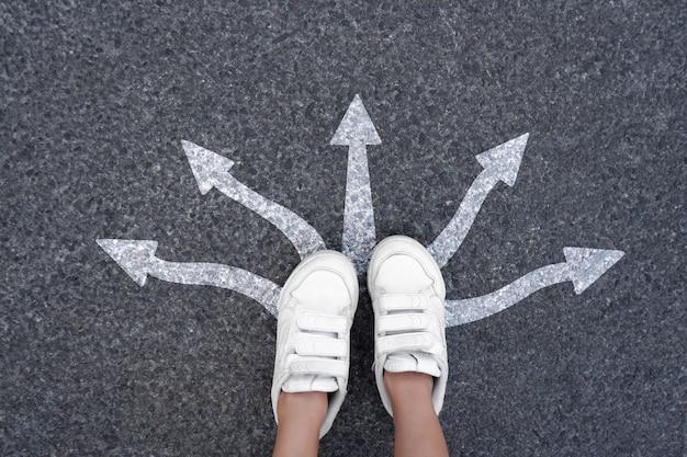 Pés andando com muitas setas de direção. futuro tênis vista superior estrada ou caminho para o sucesso.