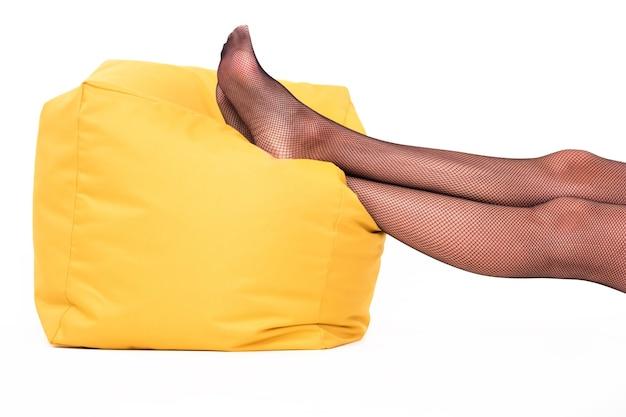 Pés apoiados no travesseiro. pernas usando meia arrastão. tire a roupa e relaxe. a senhora quer descansar.