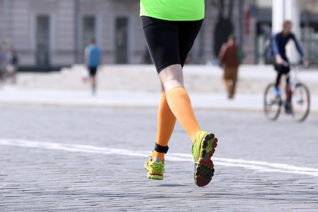 Pés atleta de longa distância em calçada de pedra