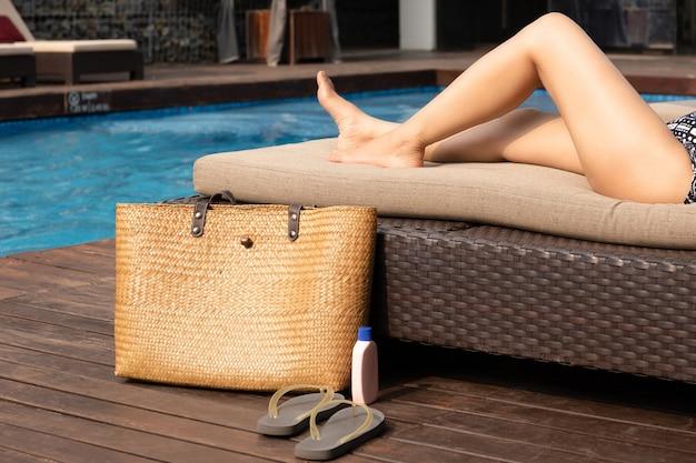 Pés bonitos da mulher que encontram-se no sunbed com saco da praia e proteção solar e sandália.
