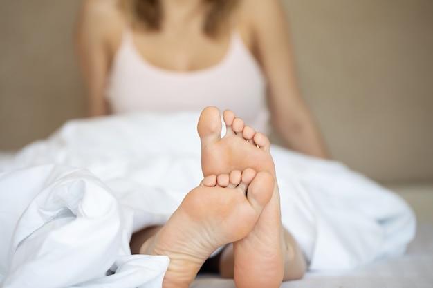 Pés bonitos de uma jovem deitada na cama de perto