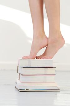 Pés bonitos em livros empilhados
