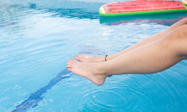 Pés bonitos flutuando em um conceito de verão de piscina transparente