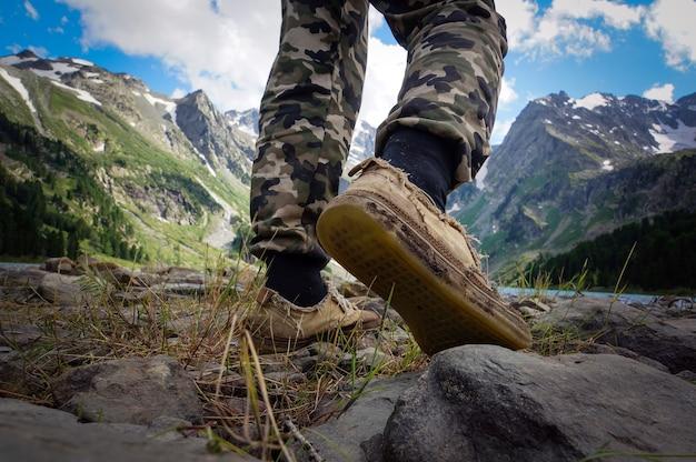 Pés botas caminhadas viajante sozinho natureza selvagem ao ar livre estilo de vida viagem conceito de sobrevivência extrema verão aventura férias passos visão única de baixo
