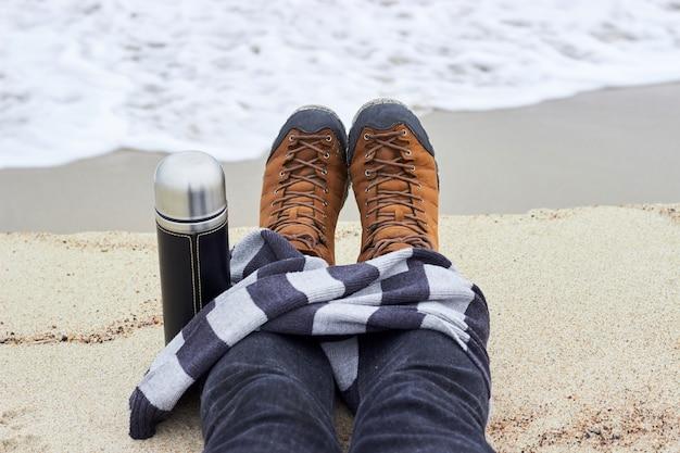 Pés com botas de trekking amarelas envolvidos em um lenço listrado com uma garrafa de água na praia