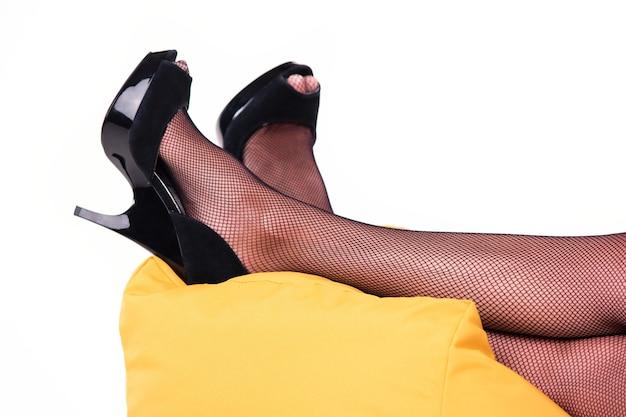 Pés com salto preto. pernas deitado sobre um travesseiro. deite por um minuto. a senhora precisa de descanso.