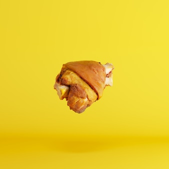 Pés da carne de porco que flutuam no fundo amarelo. conceito de comida mínima ideia.