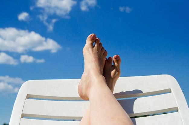 Pés da menina acima na cama de sol que relaxa na praia