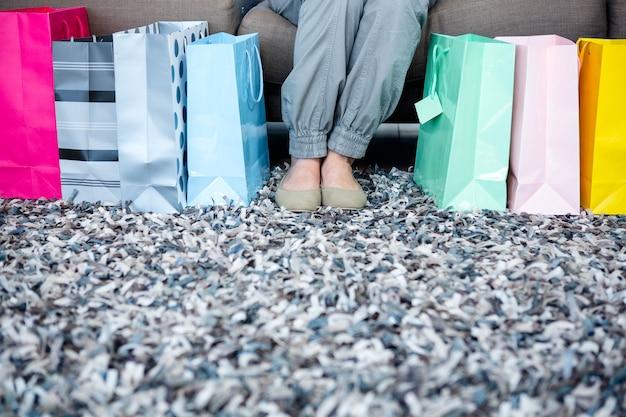 Pés da mulher cercados por sacolas de presente enquanto ela se senta no sofá