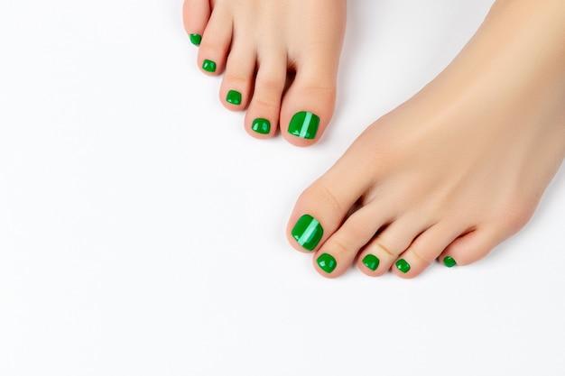 Pés da mulher com esmalte verde sobre fundo branco