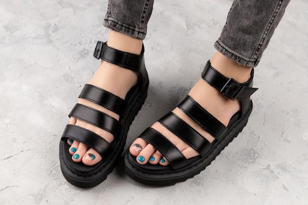 Pés da mulher com pedicure em sandálias da moda pretas sobre fundo cinza. lindo design de unhas turquesa de verão