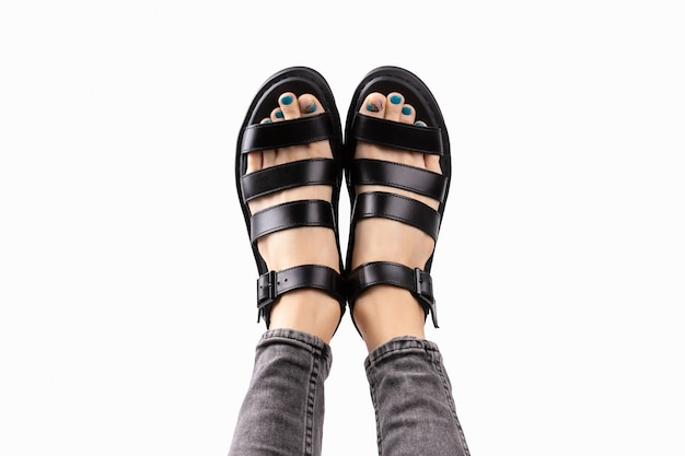 Pés da mulher com pedicure em sandálias da moda pretas sobre fundo cinza