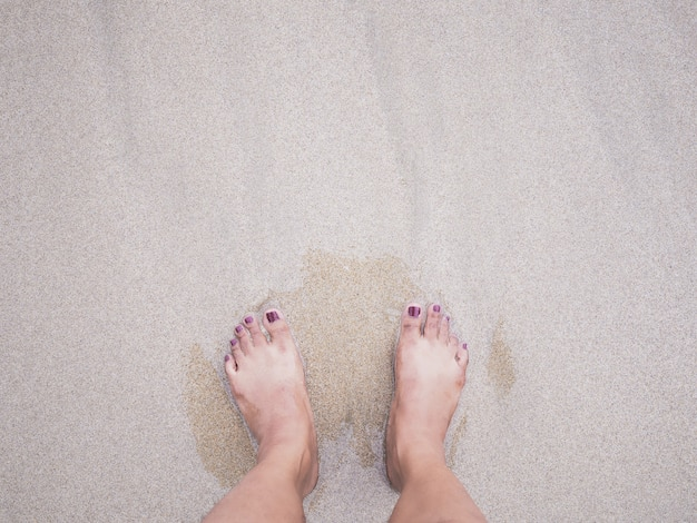 Pés da mulher de selfie no fundo da praia do verão.