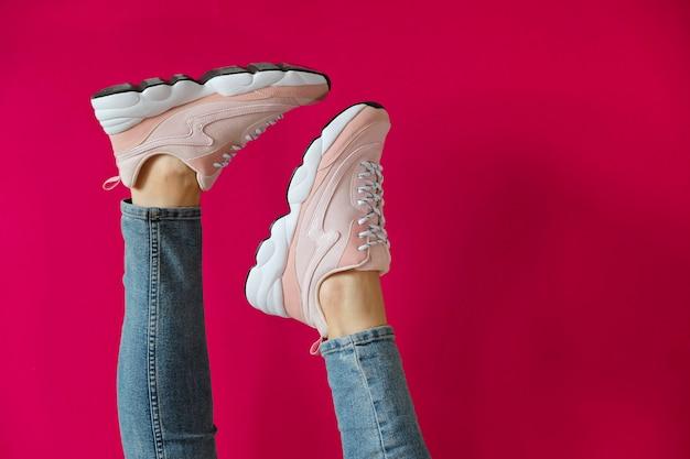 Pés da mulher em sapatos desportivos modernos sem marca