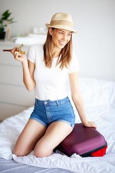 Pés da mulher levantados acima na bagagem, jovem mulher em casa que coloca na cama. o quarto branco.