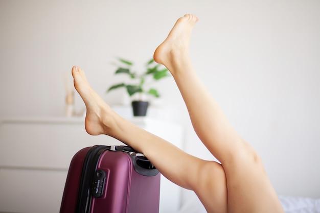 Pés da mulher levantados acima na bagagem, jovem mulher em casa que coloca na cama.