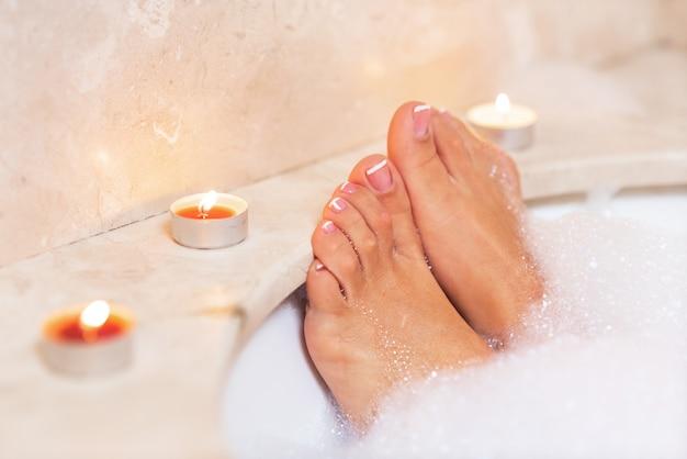 Pés da mulher na espuma do banho. relaxamento no hotel ou spa.