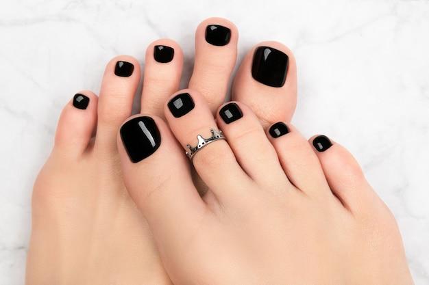 Pés da mulher no fundo de mármore. belo design clássico de unhas pretas. manicure, pedicure conceito de salão de beleza.