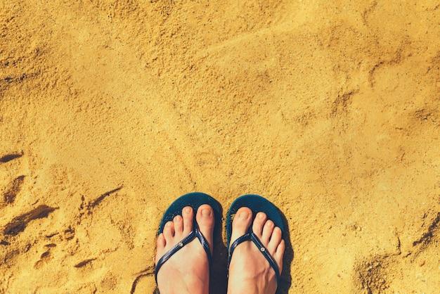 Pés da mulher nos deslizadores no fundo amarelo da areia. chinelos azuis na praia. férias e conceito de viagem