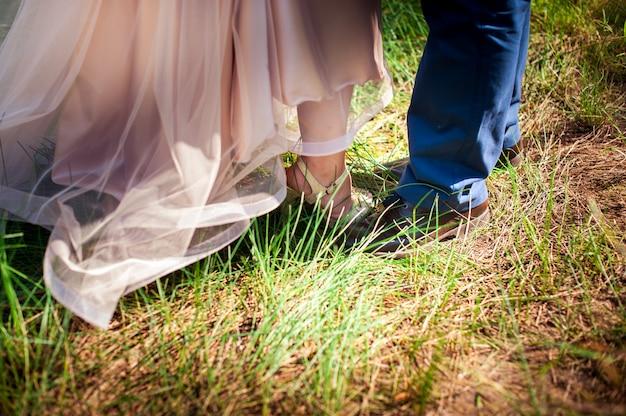 Pés da noiva e do noivo na relva verde