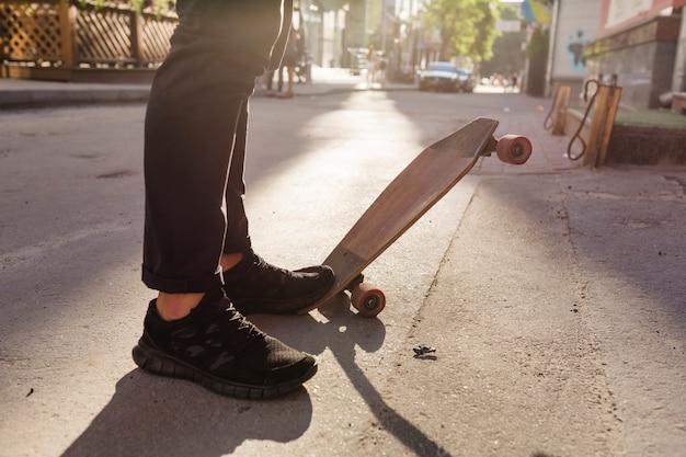 Pés da pessoa e skate de madeira na rua