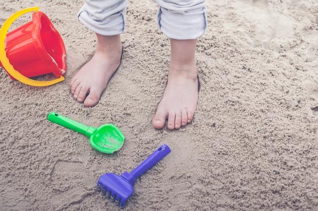 Pés das crianças no equipamento de areia e sandboxing.