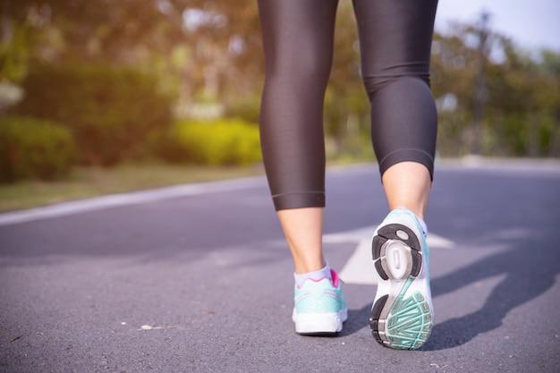 Pés de atleta corredor correndo na estrada sob a luz solar da manhã.