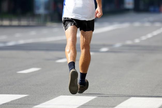 Pés de atleta correndo à distância de uma maratona. esporte e vitória