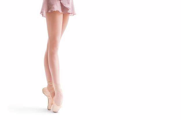 Pés de bailarina em sapatilhas de ponta isolados em um fundo branco