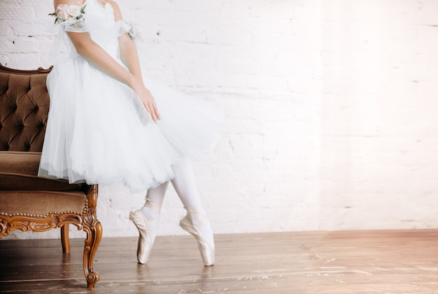 Pés de bailarina no chão do estúdio. dançarina adolescente coloca sapatilhas de balé
