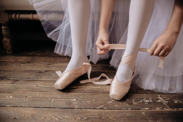 Pés de bailarina no chão do estúdio. o dançarino adolescente põe sobre copyspace das sapatilhas de balé.