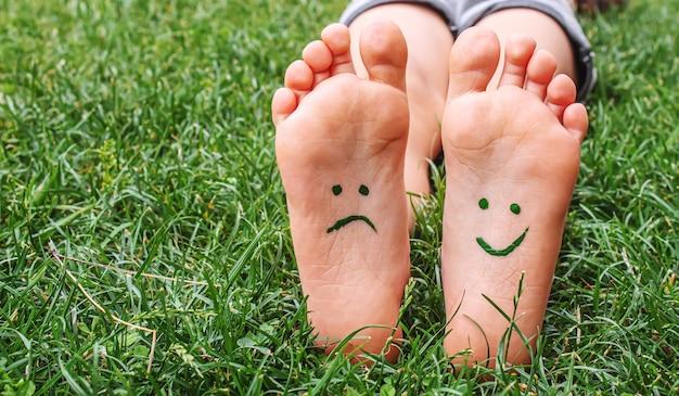 Pés de bebê com padrão de pintura estão sorrindo e tristes na grama verde. foco seletivo.