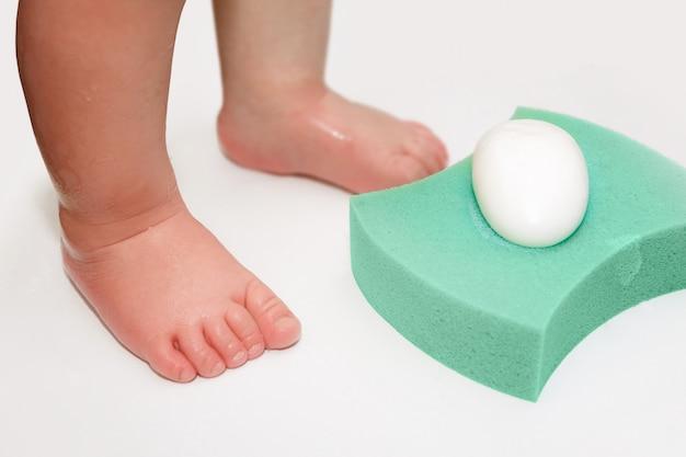Pés de bebê, esponja e sabonete na banheira
