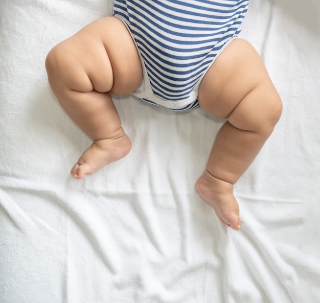 Pés de bebê na cama branca.