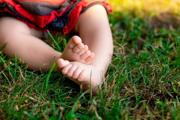 Pés de bebê na grama verde, espaço para texto