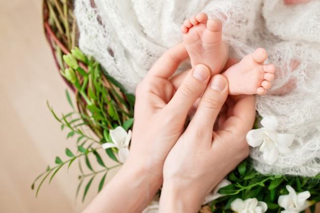 Pés de bebê nas mãos da mãe. mãe e filha. família feliz . maternidade bonita