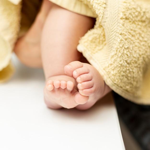 Pés de bebê pequeno close-up com toalha