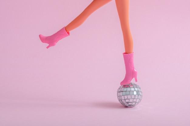 Pés de boneca em uma pequena bola de discoteca em uma parede rosa