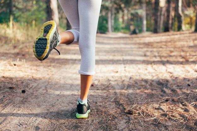 Pés de corredor correndo em close-up de estrada no sapato